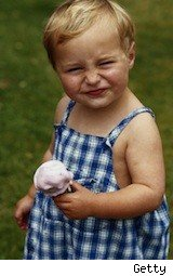 a toddler grimaces with an ice cream cone - breast millk ice cream
