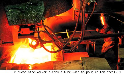 A Nucor steelworker cleans a tube used to pour molten steel. AP