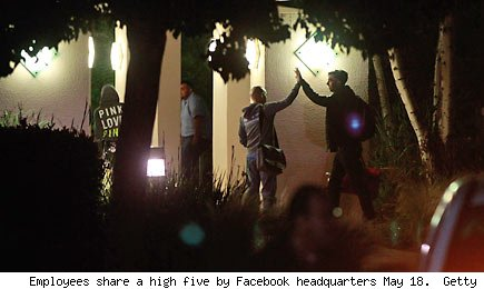 Employees share a high five by Facebook headquarters May 18. Getty