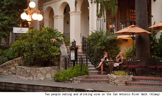 Two people eating and drinking wine on the San Antonio River Walk (Alamy)