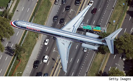 An airplane flies over an interstate highway