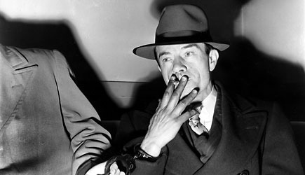 Willie Sutton smokes during questioning in Queens, New York, in 1952. (AP)