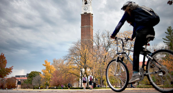 A student rides a bicycle past the bell tower on the campus of Purdue University in West Lafayette, Indiana, U.S., on Monday, Oct. 22, 2012. Photographer: Daniel Acker
