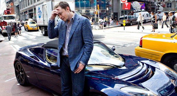 Elon Musk, chairman and chief executive officer of Tesla Motors, rubs his forehead as he stands for pictures with a Tesla Roadster outside the Nasdaq Marketsite in New York, U.S., on Tuesday, June 29, 2010. Tesla Motors Inc., the electric car company that hasn't posted a profit, raised $226 million selling shares above its forecast price range in the first initial public offering of a U.S. automaker in a half century. Photographer: Daniel Acker/Bloomberg via Getty Images