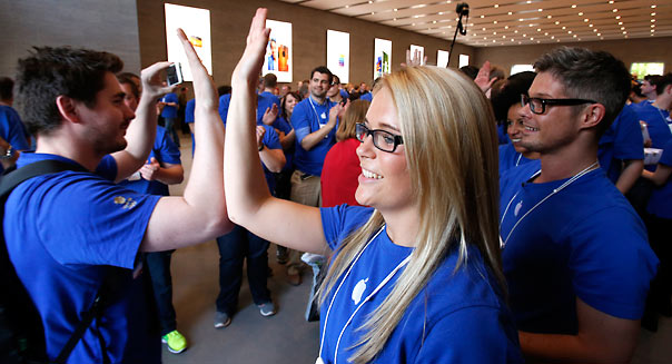 Employees welcome customers with a high five during the opening of an Apple Store at the Kurfuerstendamm shopping street in Berlin, Germany, Friday, May 3, 2013. (AP Photo/Michael Sohn)