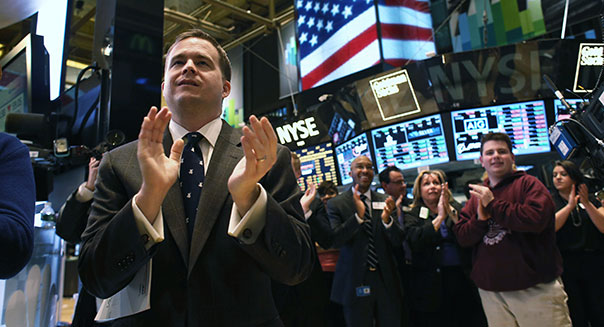People applaud at the closing bell on the floor of the New York Stock Exchange on Wall Street