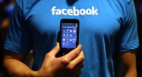 MENLO PARK, CA - APRIL 04: A Facebook employee holds a phone that is running the new