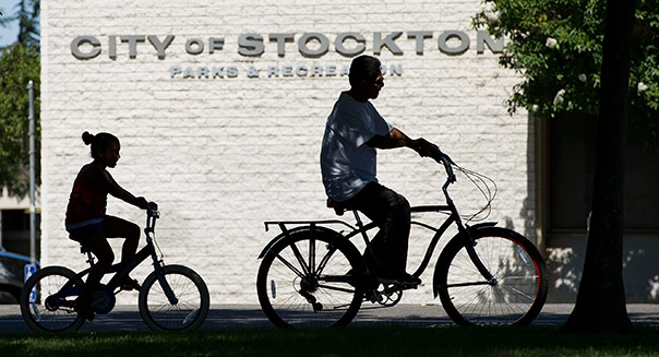 People ride bicycles along the street in Stockton, California, U.S., on Thursday, June 14, 2012. The city may have to decide next week whether to seek Chapter 9 bankruptcy protection if talks with creditors that end on June 25 don't yield concessions. Photographer: David Paul Morris/Bloomberg via Getty Images