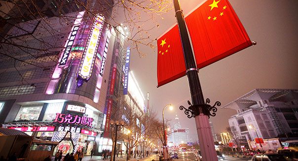 Chinese national flags fly outside a department store at night in the East Nanjing Road shopping area of Shanghai, China. Photographer: Tomohiro Ohsumi/Bloomberg