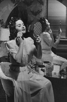 woman-putting-on-make-up-in-mirror