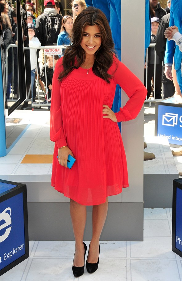 Well red: Pregnant Kourtney Kardashian dresses up for phone launch