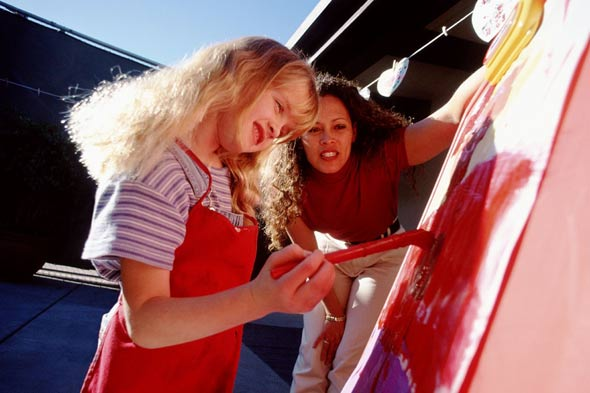 Little girl painting watched by mother