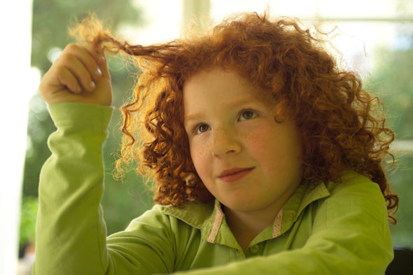 Red headed girl playing with her hair