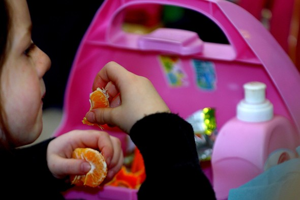 Child eating packed lunch - containing fruit