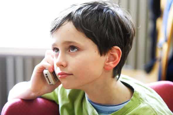 Young boy chatting on mobile phone