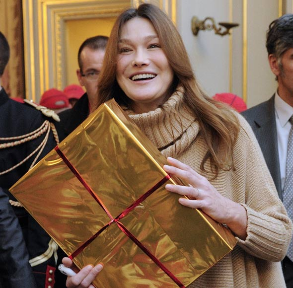 Carla Bruni-Sarkozy gives out presents to children - but baby Giulia is nowhere to be seen