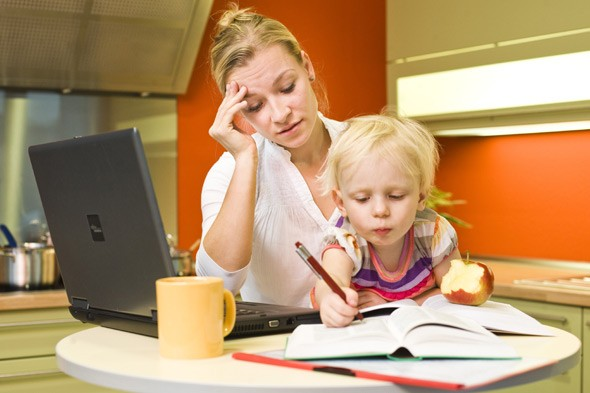Mother looking at laptop with child on lap