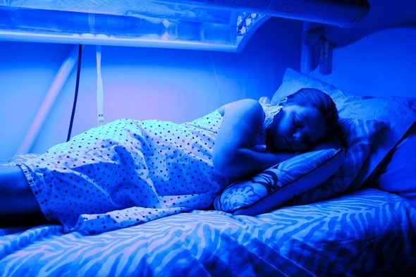 Little girl sleeps under BLUE lamps to stop her turning YELLOW