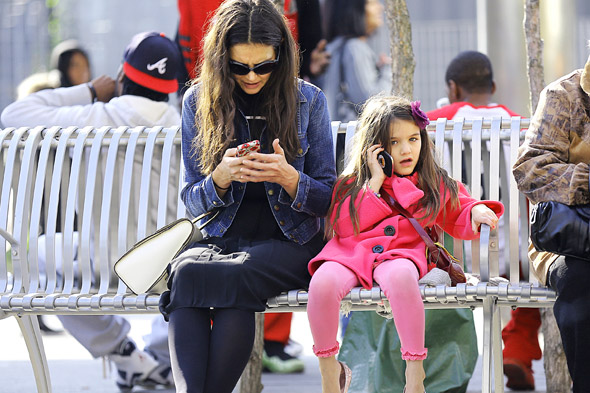 Suri Cruise sits chatting on mobile on park bench - before meeting up with boyfriend