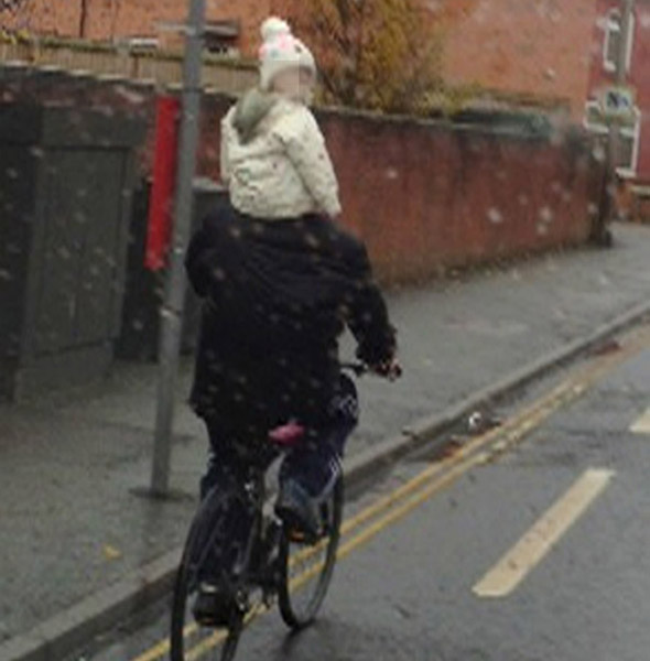'Accident waiting to happen': Man cycling on a busy road with child on his SHOULDERS