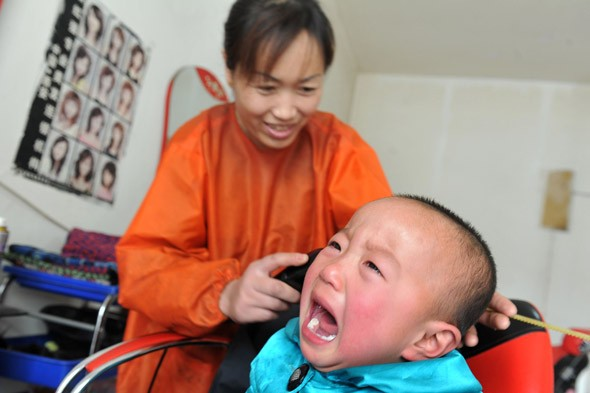'It'll grow back!' Chinese twins have meltdown after being given Mohican haircuts - for good luck!