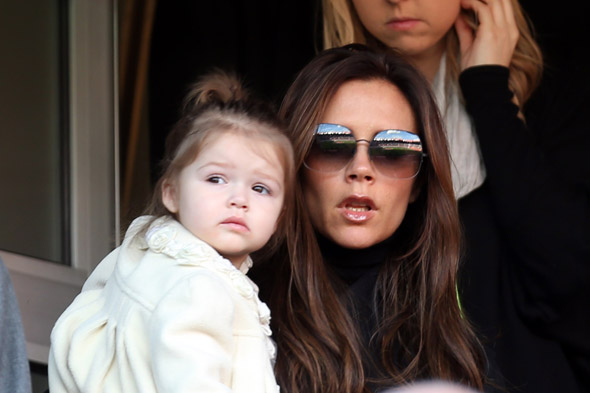 One of the boys! Harper Beckham cheers on dad David at football match