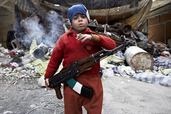Syria's chilling brutality: Boy fighter, 7, smokes a cigarette as he wields high-powered rifle