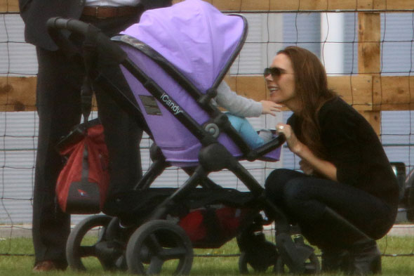 Victoria Beckham smiles - and Harper falls out of her pram