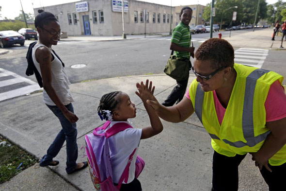 Police guards escort kids to school on gang boundary routes