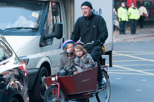 Despite cyclists' deaths dad takes girls to school in wheelbarrow on front of his bike